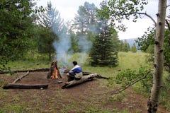 Riscaldando dal fuoco di accampamento Fotografia Stock