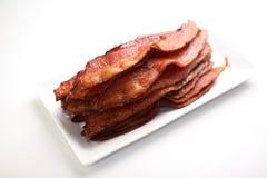 Riscaldi il bacon magro su un piatto bianco Immagine Stock