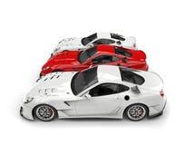 Riscaldi l'automobile sportiva rossa in mezzo a due automobili bianche Fotografie Stock
