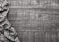 Riscaldi la sciarpa molle della lana su struttura di legno del fondo Immagine Stock