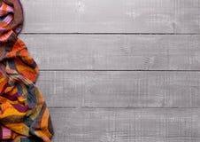 Riscaldi la sciarpa molle della lana su struttura di legno del fondo Fotografia Stock