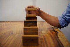 Rischio e strategia di pianificazione in uomo d'affari che gioca disponendo woode Fotografia Stock