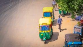 Risciò automatico giallo a Nuova Delhi, India sulla strada fotografie stock