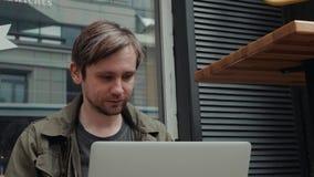 Riscrittura caucasica sorridente dell'uomo nella rete sociale con il suo amico tramite computer portatile mentre riposando nel de video d archivio