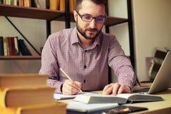 Riscrittura dell'uomo d'affari da un libro e da un computer portatile immagine stock