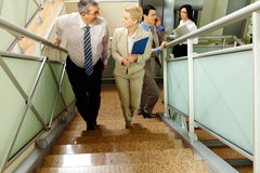 Rise. Image of successful business people going upstairs and communicating in office building royalty free stock photo