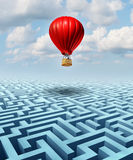 Rise Above. The challenges of business and life concept with a red hot air balloon with a businessman inside flying over a confusing maze or labyrinth puzzle as Royalty Free Stock Photos