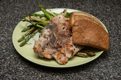 Rise, brown bread, pork steak and asparagus served on green plate Royalty Free Stock Images