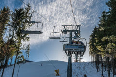 The rise in the chair lift to the top of the mountain. Stock Photography