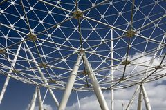 The Rise metalic sculpture in Belfast with sky and clouds in the background. The Rise intricate pipe sculpture perspective from below watching the dark blue sky Stock Image