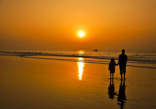 Silhouette of a man and a kid watching sunrise at. Rise like the sun and enlighten all -Father to Daughter watching sunrise in Puri beach, India Royalty Free Stock Images