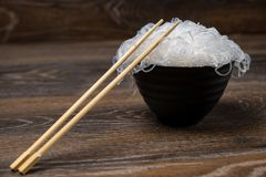 Rise noodles in black bowl on wooden background. Rise asian noodles in black bowl on wooden background Royalty Free Stock Photo