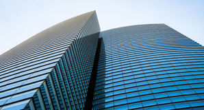 Blue glass office build rising into clear sky Royalty Free Stock Photo