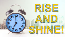 Rise and Shine text with blue alarm clock Royalty Free Stock Image
