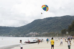 On the rise in the sky large parachute in the blue sky tropical beach. Two Chinese tourists flying on a parachute over the sea on Stock Photo