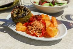 Rise stuffed fresh tomato and pepper in greek tavern. Rise stuffed fresh tomato and pepper sarved with potatoes, carrots on white wooden table in greek tavern Royalty Free Stock Photo