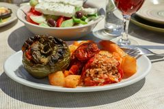 Rise stuffed fresh tomato and pepper in greek tavern. Rise stuffed fresh tomato and pepper sarved with potatoes, carrots on white wooden table in greek tavern Royalty Free Stock Photography