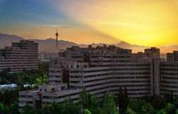 Rise. Sunrise at the Ekbatan Complex in Tehran, Iran. The mountain creating the gigantic light shaft is mount Damavand, which is 5610 meters tall Royalty Free Stock Images