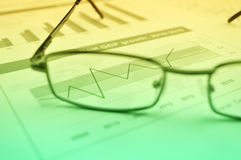 Rise up graph with glasses on financial chart and graph, Success Stock Photo