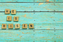 He is Risen Christian blocks on a blue wood plank background. He is Risen Christian wood blocks on a rustic wood plank background Royalty Free Stock Photo