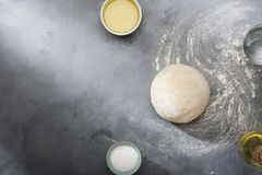 Risen or proved yeast dough for bread or pizza on a floured slate surface. Top view royalty free stock image