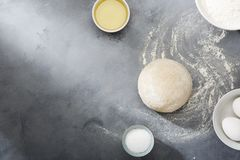 Risen or proved yeast dough for bread or pizza on a floured slate surface. Top view stock photo