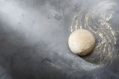 Risen or proved yeast dough for bread or pizza on a floured slate surface. Top view stock images
