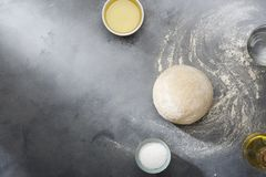Risen or proved yeast dough for bread or pizza on a floured slate surface. Top view royalty free stock images