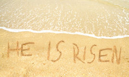 He is risen written in the sand for easter Royalty Free Stock Image