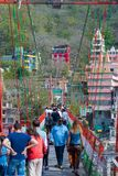 Rishikesh, Inde - 10 mars 2017 : Les gens croisant le Gange sur la passerelle de suspension chez Rishikesh, Inde, ville sacrée Images libres de droits