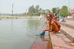 RISHIKESH, INDIA- APRIL 17, 2017: Sadhu washing his clothes in t. He river Ganges in India Royalty Free Stock Image