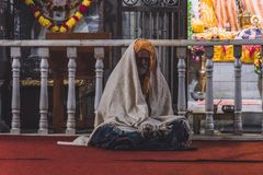 Indian sadhu, holy man sitting in front of a Hindu temple royalty free stock photos