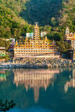RISHIKESH, INDIA -Noveber 2012: Tera Manzil Temple view from the other Ganga bank with a mirror reflection in the water. royalty free stock photo