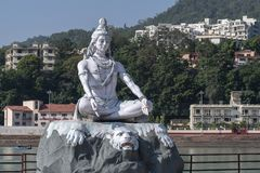 Statue of Shiva, Hindu idol near Ganges River water, Rishikesh, India. The first Hindu God Shiva. Sacred places for pilgrims. RISHIKESH, INDIA - NOVEMBER 06 stock image