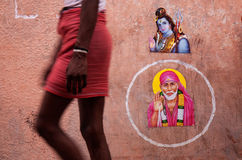 RISHIKESH STREET SCENE. A man wearing a lunghi passes religious pictures on a public wall in Ram Jula, Rishikesh, India Stock Image