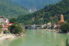 Himalayan evening mountains. Rishikesh view - indian sacred town in Himalayan mountains with ancient bridge and temple and sacred Ganga river with rafting boats Stock Images