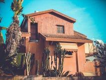 RISHON LE锡安, ISRAEL-NOVEMBER 30日2017年:一个美丽的砖色房子用大仙人掌临近它 一个大大厦 图库摄影