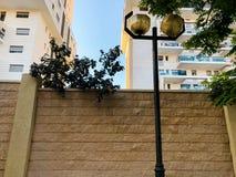 RISHON LE ZION, ISRAËL - 23 AVRIL 2018 : Haute barrière en pierre de brique à la maison et derrière elle un gratte-ciel Photo libre de droits
