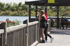 RISHON LE ZION, ISRAEL -APRIL 14, 2018: People walk along a wooden walking bridge near the lake in Rishon Lezion, Israel. RISHON LE ZION, ISRAEL -APRIL 14, 2018 Royalty Free Stock Images