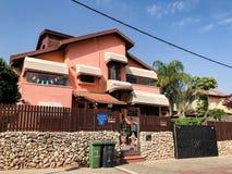 RISHON LE ZION, ISRAEL - 30 DE ABRIL DE 2018: Uma casa colorida bonita com a cerca de madeira e de pedra grande e as grandes árvo Fotos de Stock