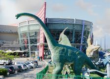 Dinosaurs land in front of Cinema city stock images