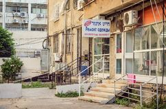 The rent apartment building with tailoring repairs sign in Russian and Hebrew. Rishon LeZion, Israel-June 23, 2017: Low- income neighborhood with neglected old Royalty Free Stock Photos