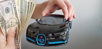 A man holds in his hand in the air Black Bugatti Chiron car metal toy while other person gives him a bundle of money royalty free stock photography