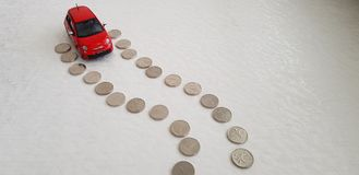 Red fiat 500 abarth toy starting its way on road line made of one Israeli shekel coins stock photos