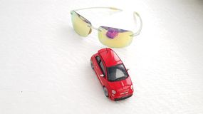 Small red Fiat 500 toy rear view reflected in sunglasses royalty free stock photography