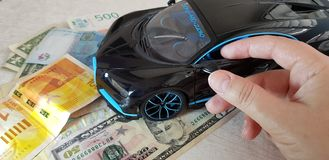 Young girl touches with her fingers a mirror of Black Bugatti Chiron metal toy standing with front wheels on paper money stock photography