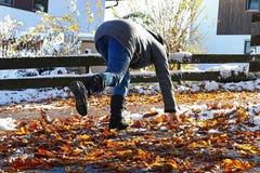 Risico om in de herfst en de winter uit te glijden Een vrouw gleed op natte, vlotte bladeren uit royalty-vrije stock afbeelding