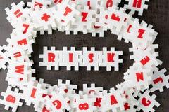Risicobeheerconcept, witte raadselfiguurzaag met alfabet die het woordrisico bouwen op het centrum van donker bord royalty-vrije stock fotografie
