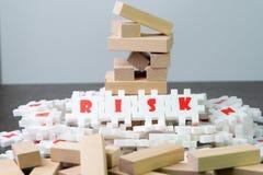 Risicobeheerconcept, witte raadselfiguurzaag met alfabet die het woordrisico bouwen op het centrum van donker bord met instorting royalty-vrije stock foto's