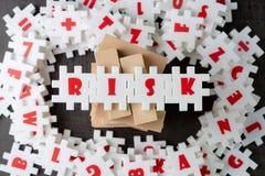 Risicobeheerconcept, witte raadselfiguurzaag met alfabet die het woordrisico bovenop houten toren bouwen op het centrum van dark royalty-vrije stock afbeeldingen